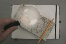 magnifying glass over a map on a journal
