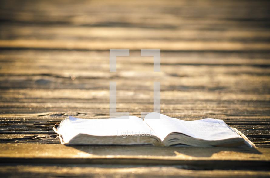 Open Bible on a wooden deck.