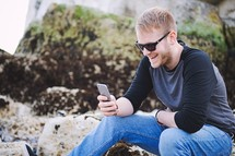 a man sitting on a rock texting on a cellphone