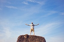a man with outstretched arms standing on a hay bale
