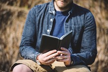 a man reading a Bible sitting on rocks