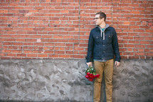 Looking for love -- a man standing by a brick building with a bouquet of roses in his hand.