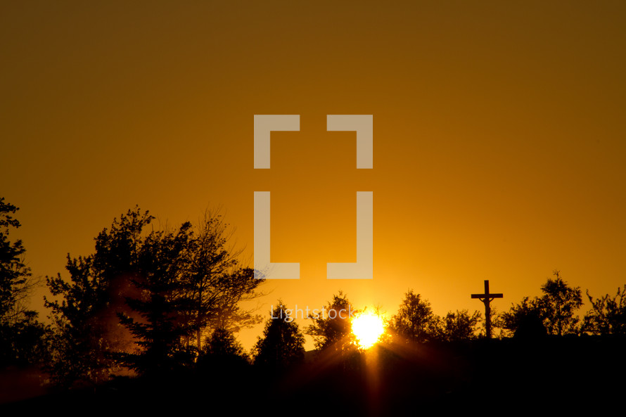 sun setting behind the trees and a silhouette of a cross