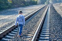 boy child walking alone on railroad tracks