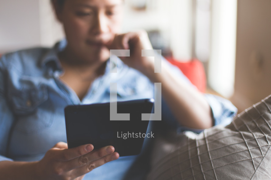 A woman reading a Bible on her tablet