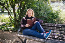 woman reading a Bible while sitting on a park bench