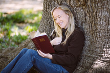 woman reading a Bible under a tree