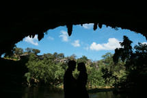 silhouette of a couple hugging in a cave