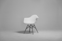 A plastic white chair in an empty room.