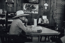 elderly man in a cowboy hat sitting in a restaurant