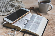 open Bible with coffee mug, cellphone, earbuds, and scarf