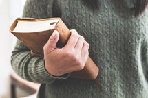 a woman in a sweater holding a Bible