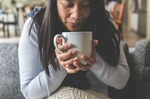 a woman holding a warm mug