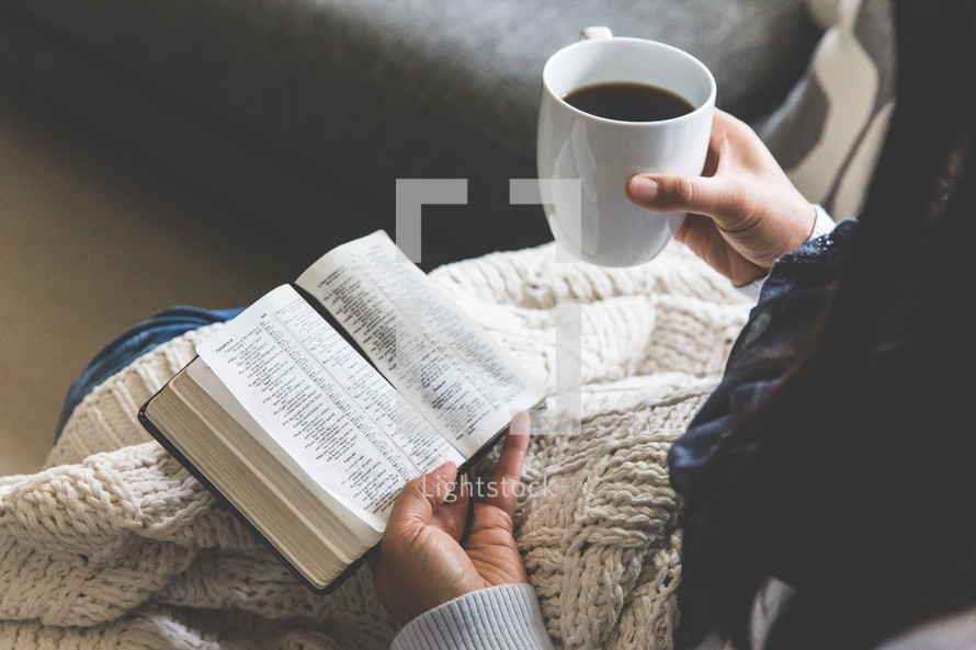 a woman reading a Bible wrapped up in a blanket