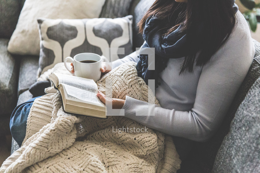 a woman reading a Bible snuggled in a blanket