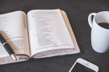 pen on an open Bible and coffee mug