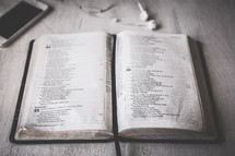 iPhone, earbuds, and open Bible