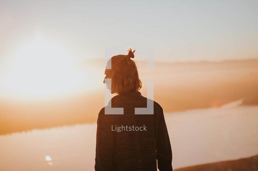 a man standing outdoors under bright sunlight