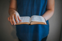 a woman standing reading a Bible