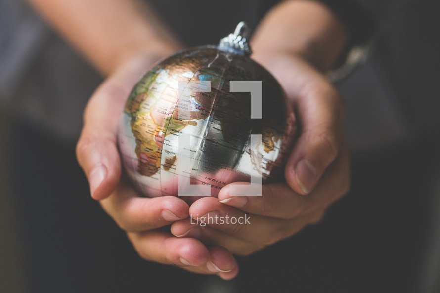 cupped hands holding a globe ornament