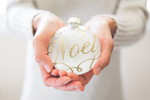 a woman holding an ornament with the word noel on it