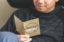 a man reading a Christmas greeting card