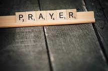"""""""Prayer"""" spelled in Scrabble tiles."""