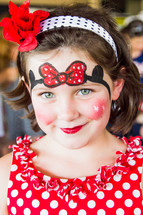 girl child with Minnie Mouse face paint