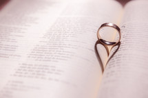 a wedding band forming a shadow in the shape of a heart between the pages of a Bible