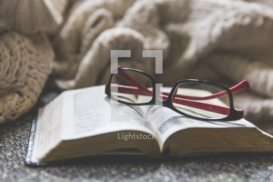 reading glasses, open Bible, and blanket on a couch