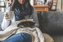 a woman reading a Bible under a blanket