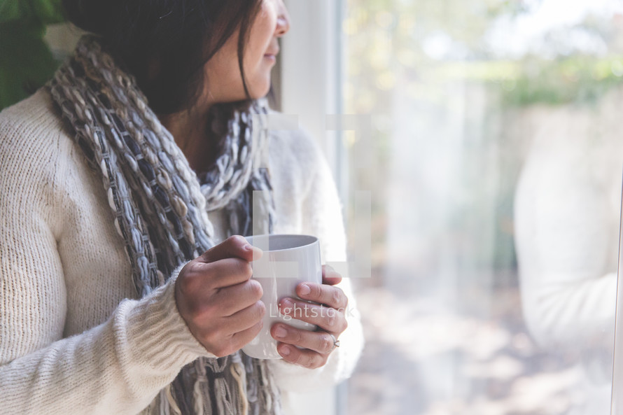 a woman holding a coffee mug and looking out a window