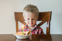 toddler boy with a birthday cupcake in a bowl