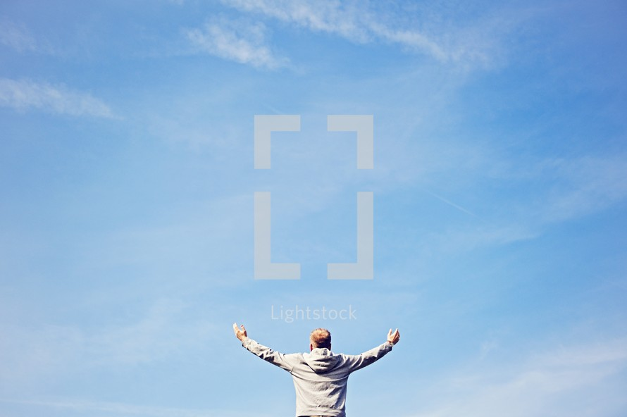 a man with raised hands against a blue sky