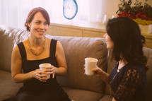 Two women talking together on a couch, with coffee.