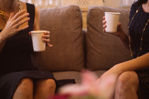 Two women drinking coffee and talking together on a couch.