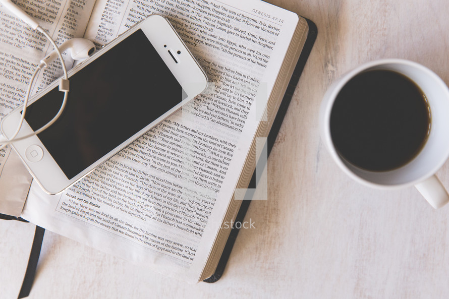 iphone, earbuds, on the pages of an open Bible