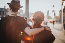 a man walking down a sidewalk with his arm around a woman