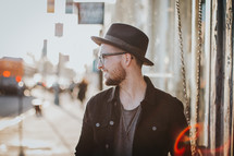 side profile of a man with a hat and beard standing on a sidewalk