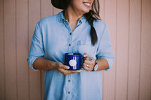 a woman standing holding a coffee mug