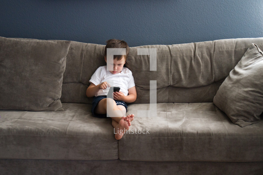 boy child with a cellphone on a couch