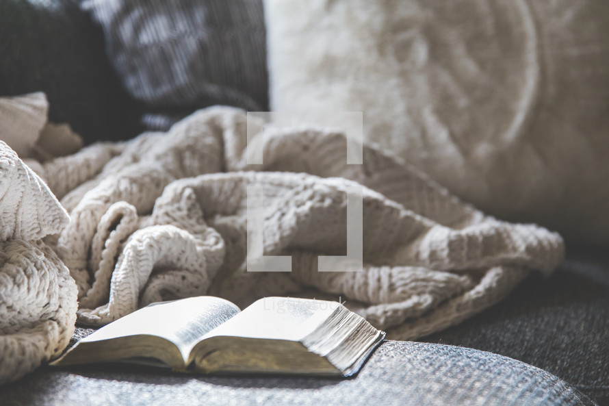 open Bible and blanket on a couch