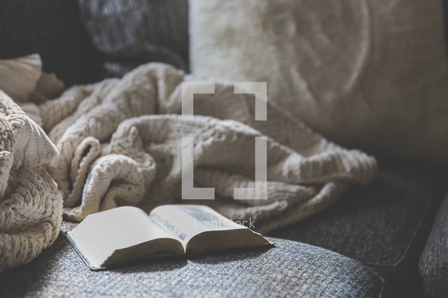 blanket and open Bible on a couch