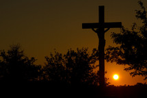 sun setting behind a sculpture of the crucifixion of Christ