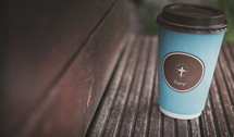 coffee cup with cross on wood ledge