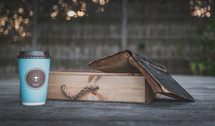 coffee cup with cross on wood ledge with Bible and wood box