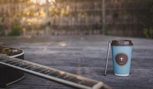 coffee cup with cross, cellphone, and guitar on wood table