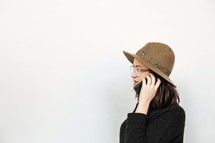 woman in a hat talking on a cellphone