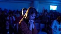 woman praying during a worship service