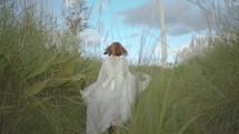 a woman in a long dress running through a field of grass